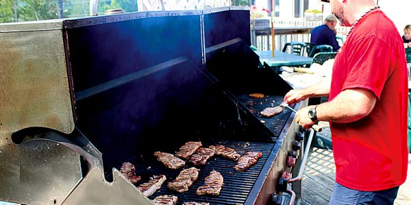 Man cooking steaks on an outdoor grill