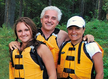 Family of three getting ready to raft down a river.