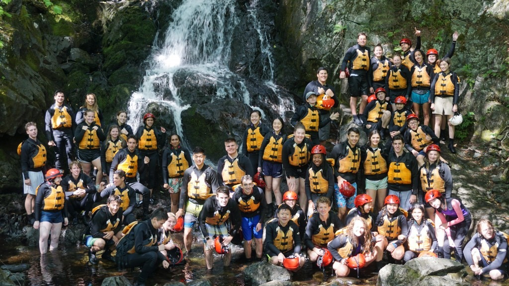 School group in rafting gear posing near a waterfall.