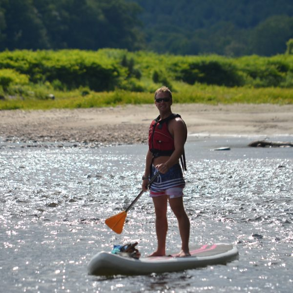 Vacationer near the shore on a stand-up paddle board.