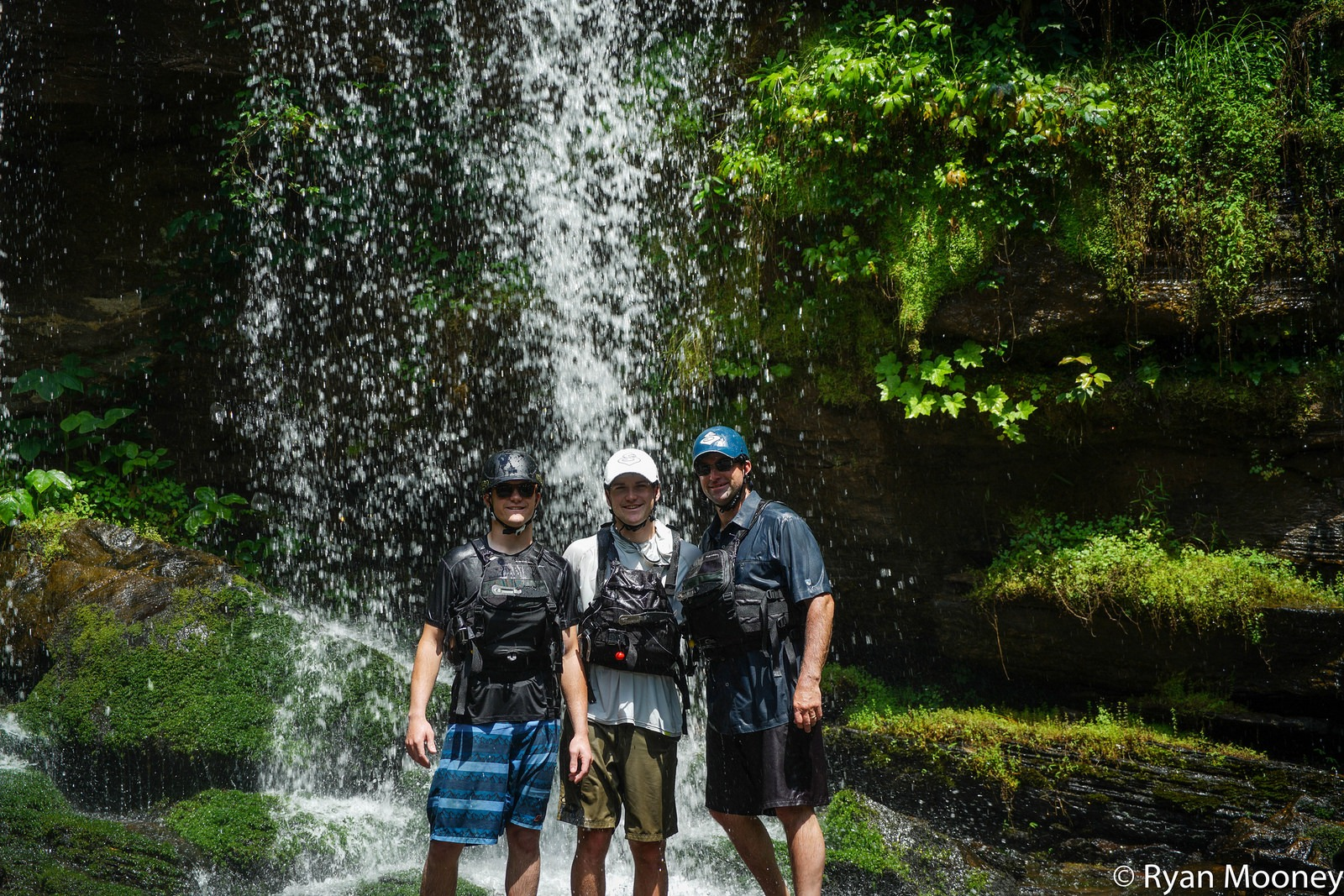 Three members of the Crap Apple team under a waterfall.